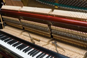 Mécanique de piano en cours de réglage. Outillage de l'accordeur de piano posé sur le clavier d'in piano droit .