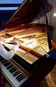 Un accordeur de piano qui accorde un piano à queue avec une clef d'accord